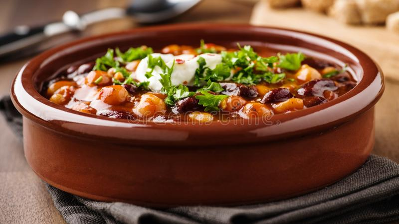 Veggie chili with chick peas and beans. Hot stew with chick peas beans, soy meat and chili peppers stock images