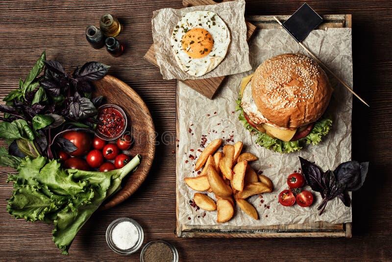 Veggie hamburger met salade, tomaat en gebraden gerechten Houten achtergrond stock afbeeldingen