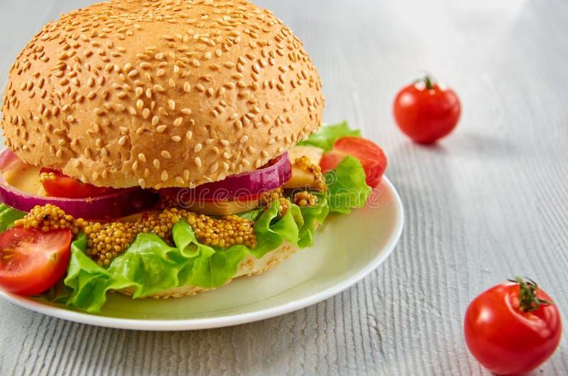 Veggie hamburger z sałatką, cebulkowi pierścionki dekorujący z świeżymi czereśniowymi pomidorami na szarość betonu tle z bezpłatn fotografia royalty free