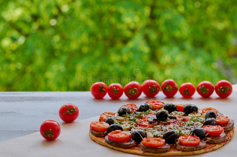 Veggie pizza with mushrooms, black olives and herbs on the gray kitchen table decorated with fresh cherry tomatoes royalty free stock images