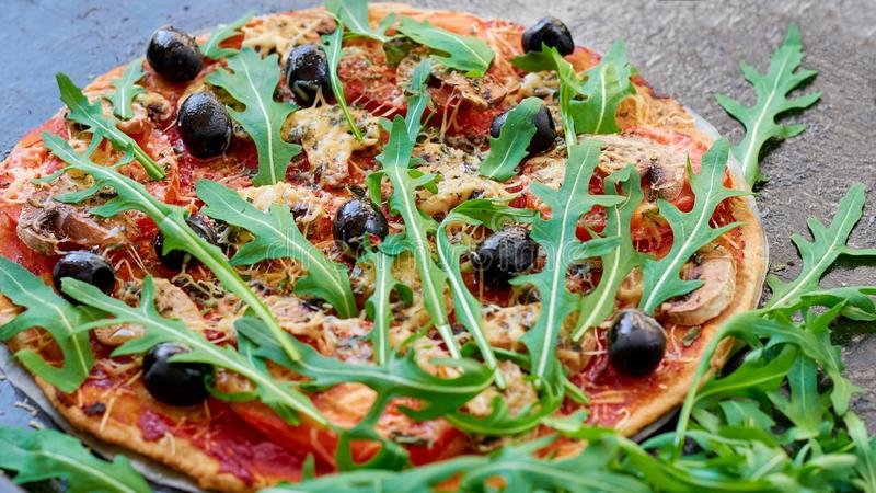 Veggie pizza with mushrooms, tomatoes, black olives on the dark background. Vegetarian pizza with vegetables and spices royalty free stock photo