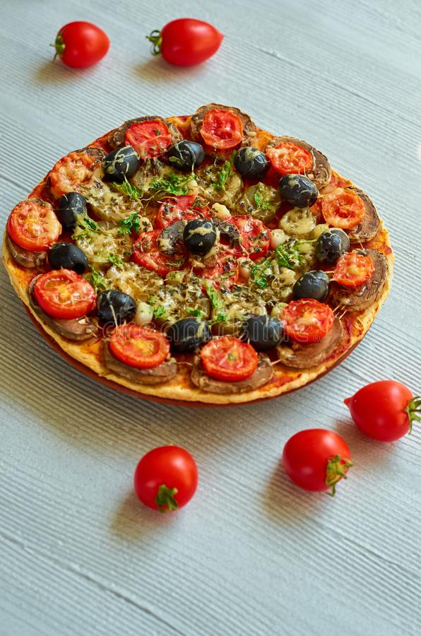 Veggie pizza with tomatoes, black olives on the gray concrete background. Vegetarian pizza with mushrooms and spices royalty free stock photography