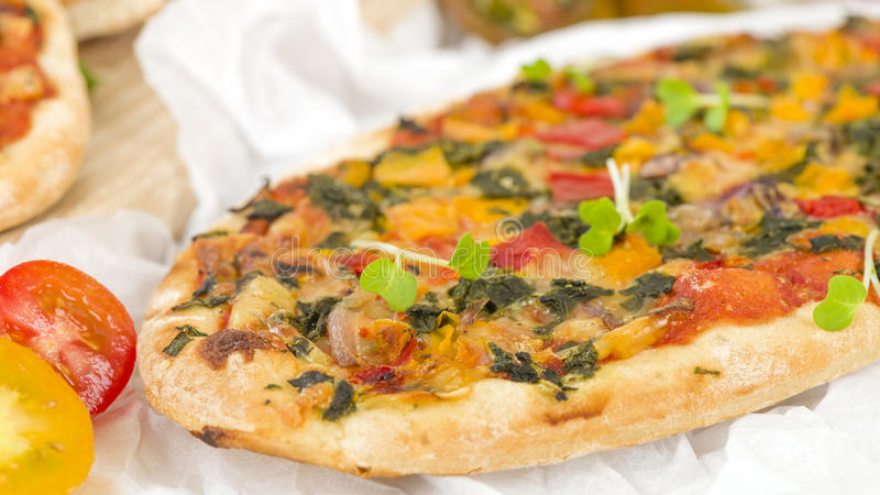 Veggie Pizza. Vegetarian mini pizza on a wooden background royalty free stock photography