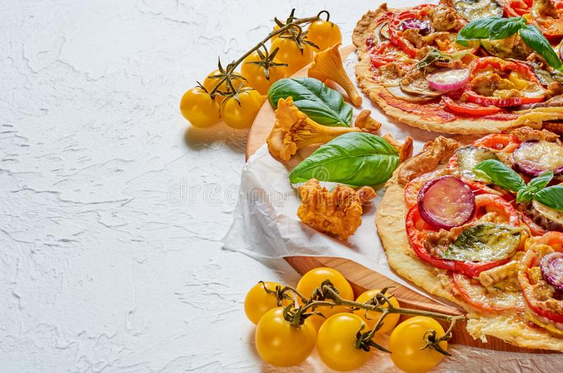 Veggie pizza with wild mushrooms, vegetables and spices on the concrete background. Vegetarian pizza decorated with tomatoes. Veggie pizza with wild mushrooms stock photo