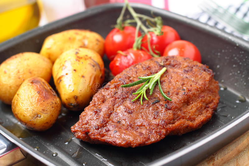 Veggie-Steak. With baked potatoes and grilled tomatoes stock photos
