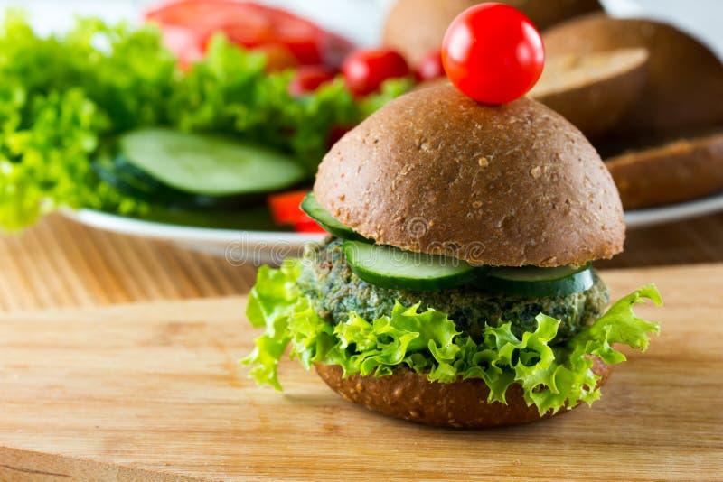Veggie szpinaka hamburgery z chlebem, ogórkiem i sałatą żyta, zdjęcie stock