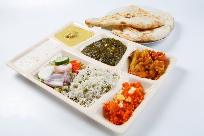 Veggie thali combo. With raita mix veggie karhi pakora palak paneer gajrella naan rice and salad stock images