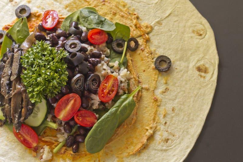 Veggie Wrap. Portobello mushroom organic veggie vegan wrap open to show ingredients royalty free stock photo