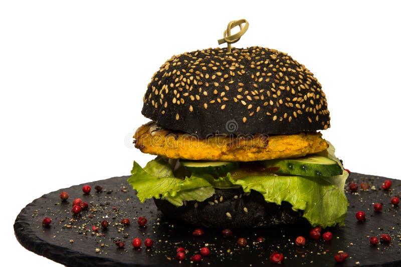 Veggie zwarte hamburger met groene salade en komkommer Ge?soleerd op wit royalty-vrije stock foto