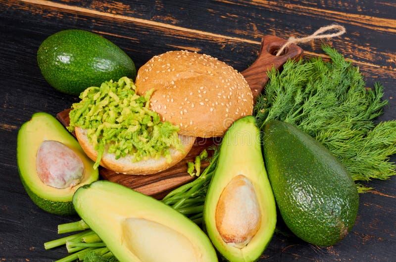 Veggieavokadosmörgås med dill på träbrädet Den traditionella sunda mexicanska maträtten - banta den gröna guacamolehamburgaren fotografering för bildbyråer