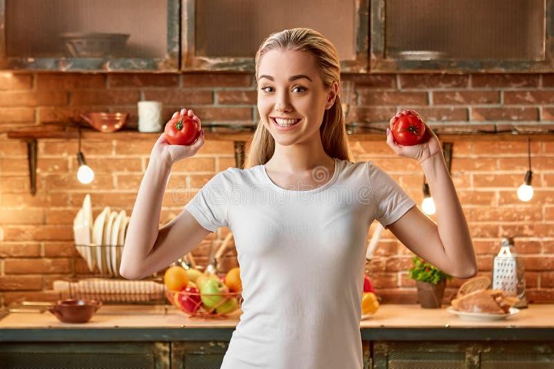 Veggies trekt t-oorzakenwiggen aan Gelukkige jonge vrouw die verse groenten in moderne keuken snijden Comfortabel binnenland stock foto's