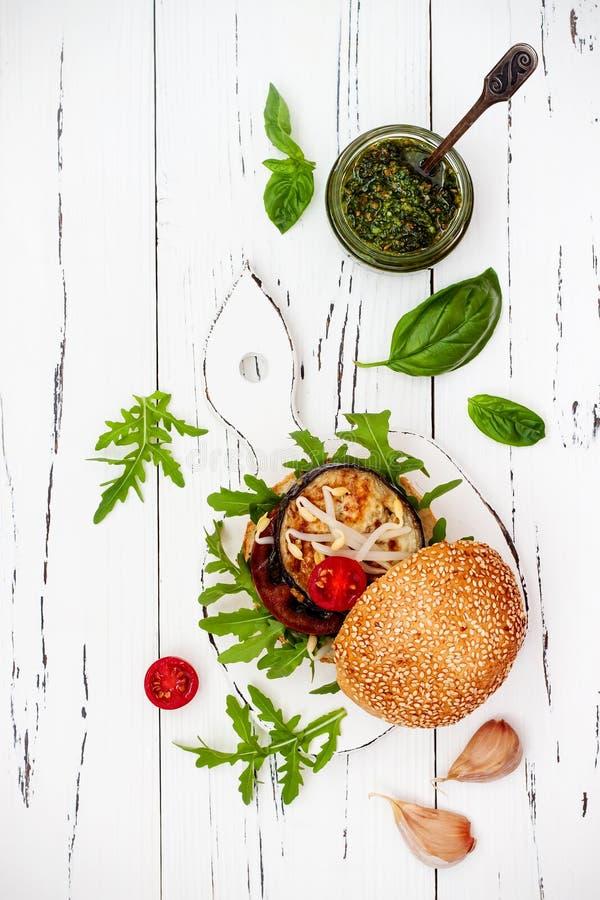 Veggieshamburgaren tjänade som på skärbräda över den vita lantliga tabellen Strikt vegetarian grillade aubergine, arugula, grodda arkivfoto