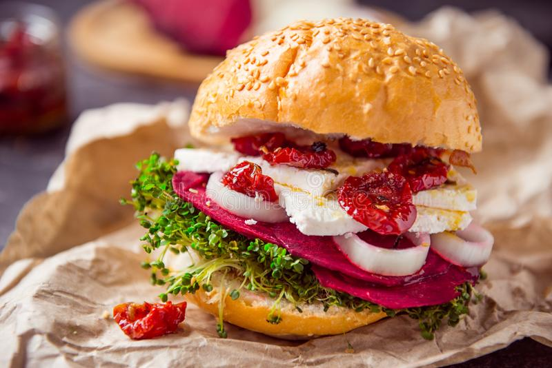 Vegitarian burger with beet slices, microgreen sprouts, tofu cheese, dried tomatoes and onion on kraft package paper on dark stone royalty free stock photography