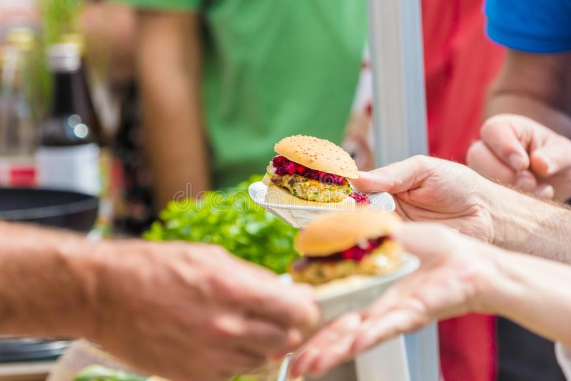 Vegitarian Burger on street food Festival. Customers in a queue royalty free stock images
