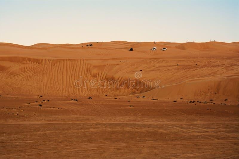 Vehículo campo a través sobre las arenas del wahiba de las dunas del desierto en la puesta del sol imagen de archivo libre de regalías