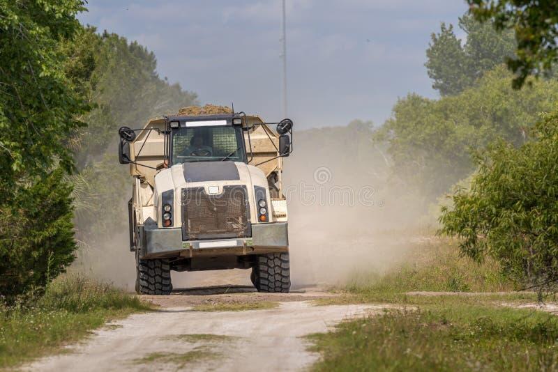 Vehículo de la construcción - razas del camión volquete abajo del camino de tierra en un área boscosa foto de archivo
