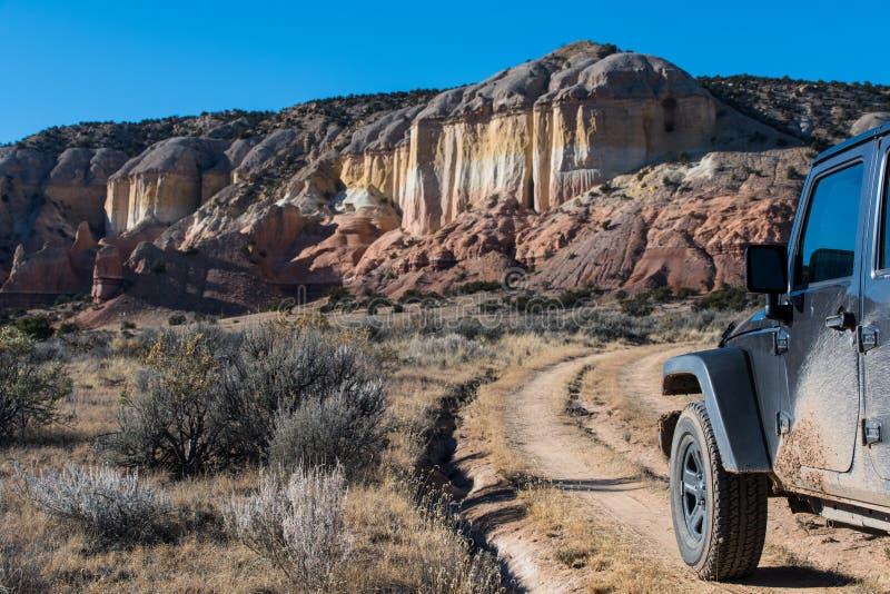 Vehículo fangoso del tracción cuatro ruedas en curvar el camino de tierra que dirige hacia un mesa colorido en un alto paisaje de foto de archivo