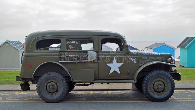 Vehículo militar americano del vintage parqueado en la 'promenade' de la orilla del mar delante de la choza de la playa imagen de archivo libre de regalías