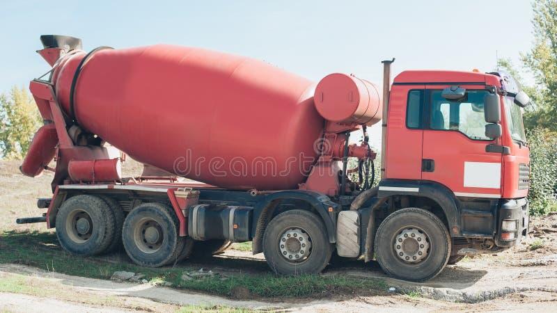 Vehículo rojo del mezclador concreto en el emplazamiento de la obra fotos de archivo libres de regalías