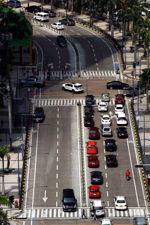 Vehículos privados y públicos en una intersección en la ciudad de Pasig, Filipinas durante la hora punta por la mañana fotos de archivo libres de regalías