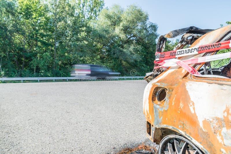 Vehículos que pasan detrás de un coche de accidente con cinta adhesiva de barrera policial con una palabra alemana para barricada foto de archivo libre de regalías