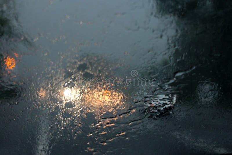 Vehículos vistos a través de un vidrio mojado bajo la lluvia fotos de archivo libres de regalías