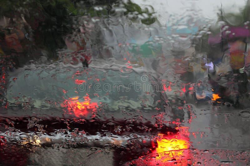 Vehículos vistos a través de un vidrio mojado bajo la lluvia foto de archivo