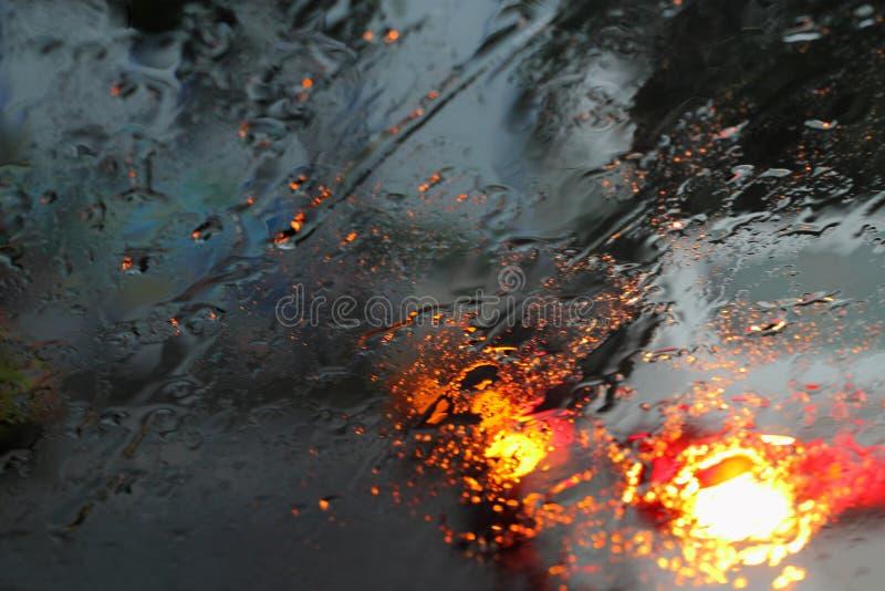 Vehículos vistos a través de un vidrio mojado bajo la lluvia foto de archivo libre de regalías