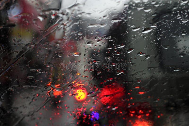 Vehículos vistos a través de un vidrio mojado bajo la lluvia fotografía de archivo libre de regalías