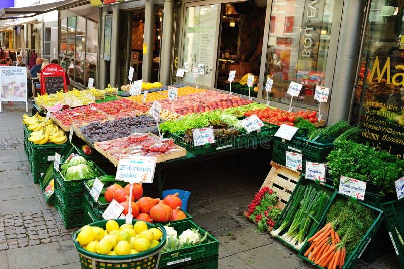 Vehículos y frutas en una parada del mercado foto de archivo libre de regalías