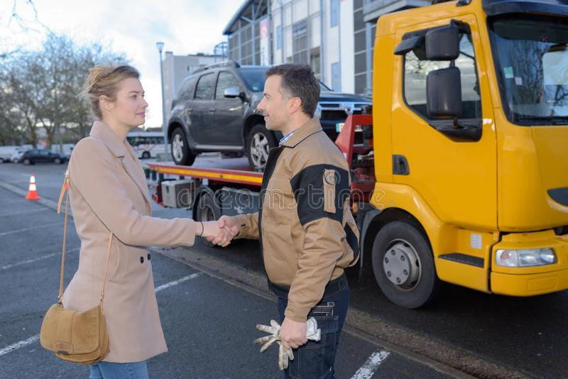 Vehicle assistance worker shaking hands with customer. Vehicle royalty free stock photography