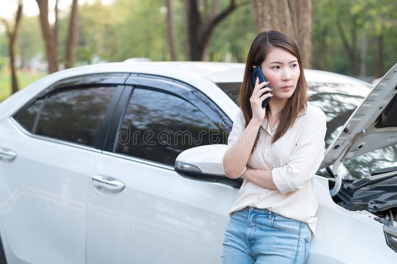 Young Asian woman calling assistance for her broken down car. Vehicle breakdown concept. Young Asian woman try to call assistance for her broken down car stock photos