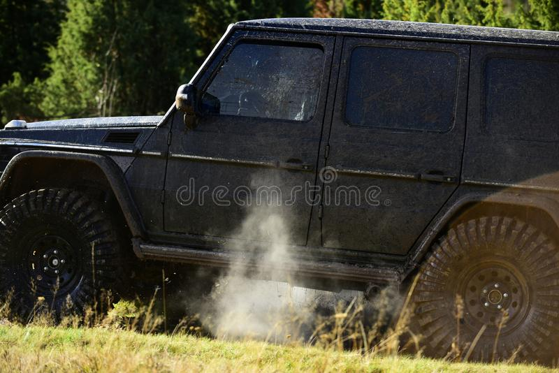 Vehicle covered with mud drops. Side of car covered with dirt and cloud of smoke. Off road racing, force and extreme. Entertainment concept. SUV on nature stock photography