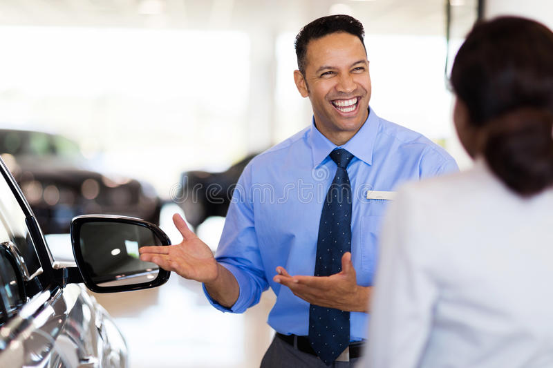 Vehicle dealer showing woman car. Friendly vehicle dealer showing young women new car royalty free stock image