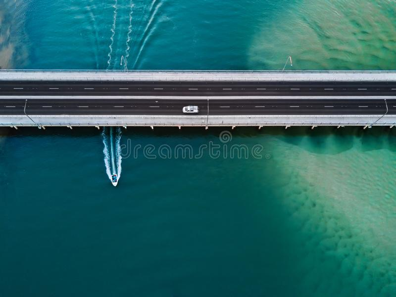 Car crosses bridge as speed boat travels under it. Aerial view stock photo