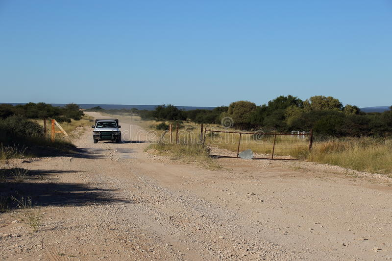 Vehicle on a dust road. A small vehicle drives on a dirt road with a cattle-grid in the Great Karoo natural region in the Northern Cape of South Africa stock image