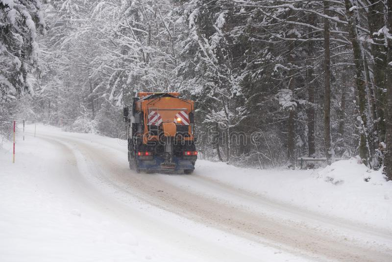 A Vehicle gritting winter road. A vehicle is gritting winter road in a snowy day and forest background royalty free stock images