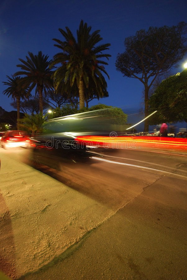 Vehicle motion blur at night. A view of the blur of lights as a car passes by on a street at night stock image