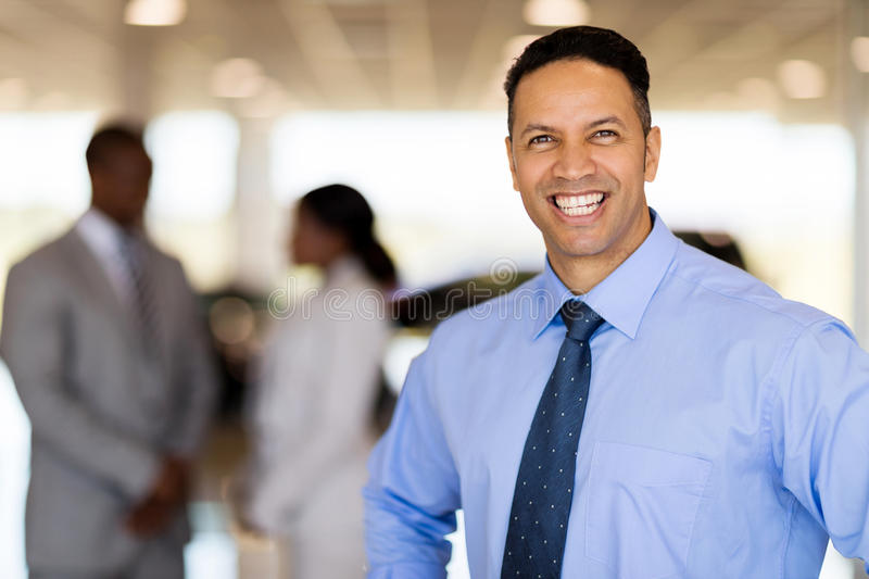 Vehicle sales consultant. Happy middle aged male vehicle sales consultant in showroom royalty free stock photo