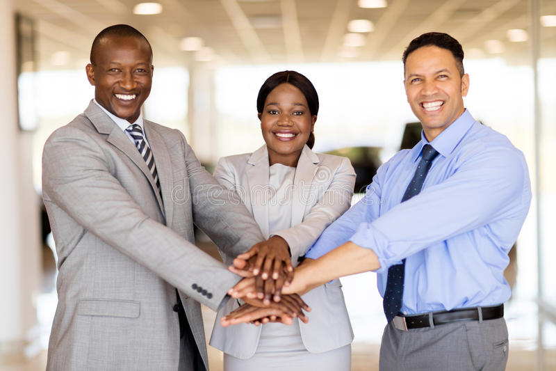 Vehicle sales team hands together. Happy vehicle sales team putting their hands together inside showroom stock photography