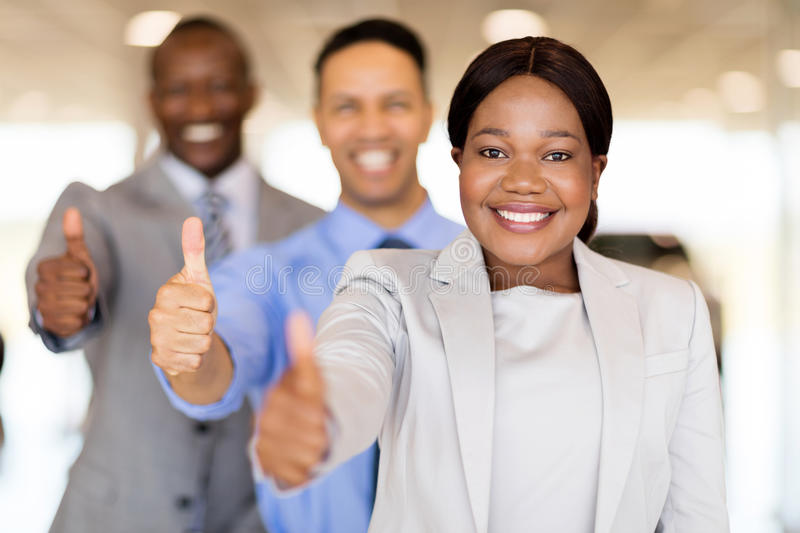 Vehicle sales team in a row. Professional vehicle sales team in a row giving thumbs up royalty free stock photography