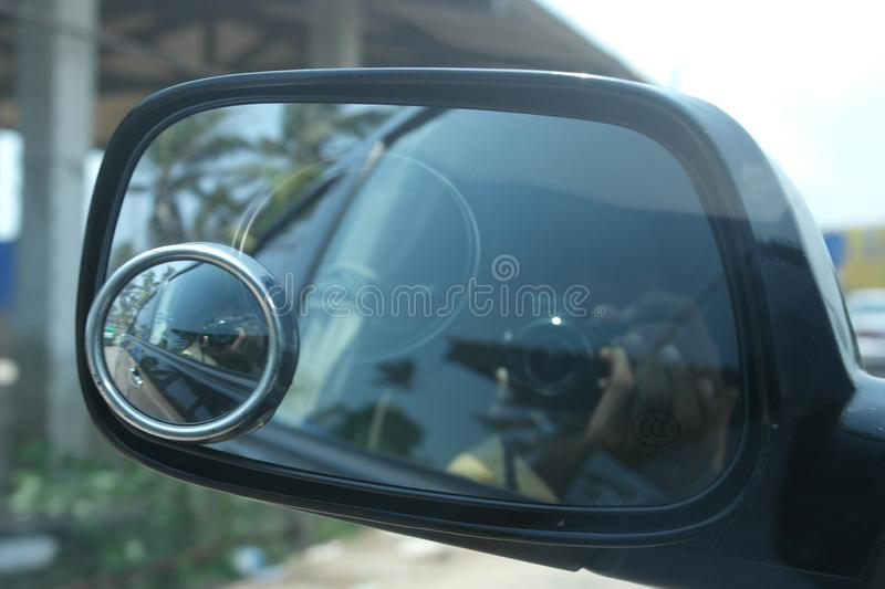 Vehicle side mirror of a car. Side mirrors are extremely common and mounted on any car, whether it is new or old stock photography