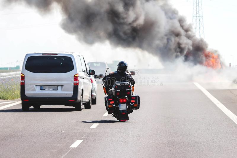 Vehicles on a highway passing a burning car. Car accident / road disaster concept. Vehicles on a highway passing a car burning with thick black smoke royalty free stock images