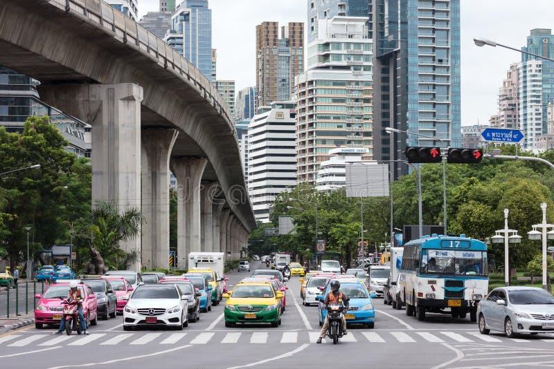 Vehicles stop at the red light. Bangkok, Thailand - August 1, 2015: Picture of vehicles stop at the red light at Sala Daeng Junction and modern high rise stock image