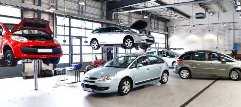Veicoli in un'officina riparazioni dell'automobile per la riparazione con il platfo di sollevamento fotografia stock