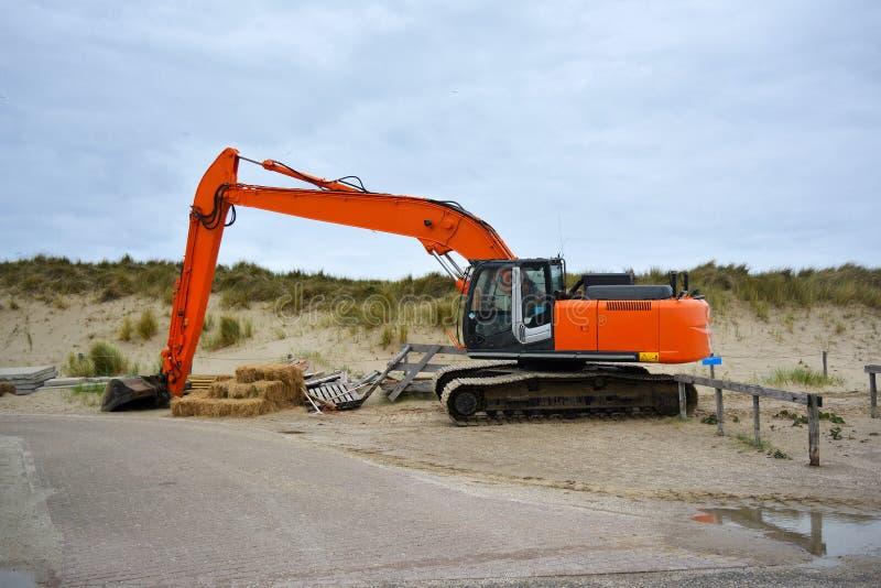 Veicolo dell'escavatore per l'accumulazione della sabbia alla spiaggia a Paal 9 dopo una tempesta pesante a Texel immagine stock libera da diritti