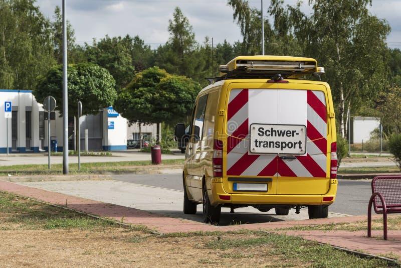 Veicolo di sicurezza per l'accompagnamento dei trasporti pesanti con il trasporto pesante dell'iscrizione fotografia stock