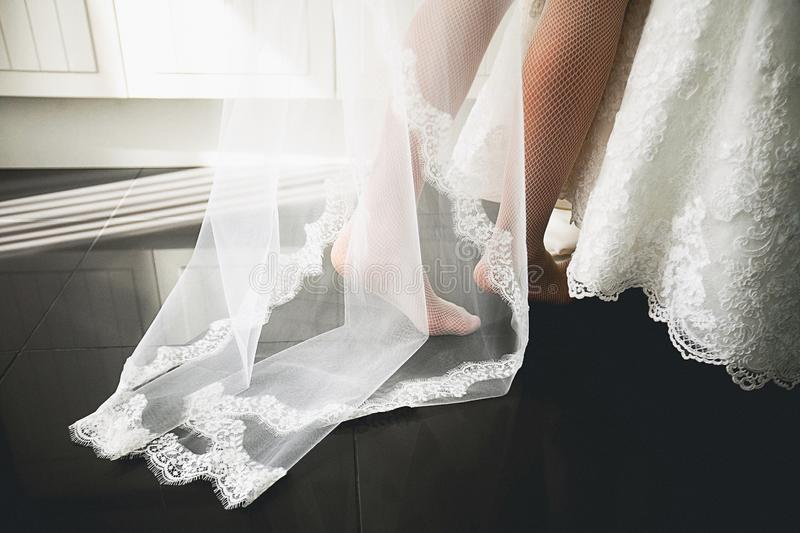 Veil, dress and feet of the bride close-up royalty free stock photo