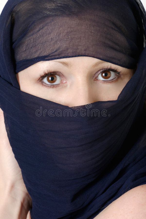 Veiled beauty. Woman with brown eyes wearing a blue face covering