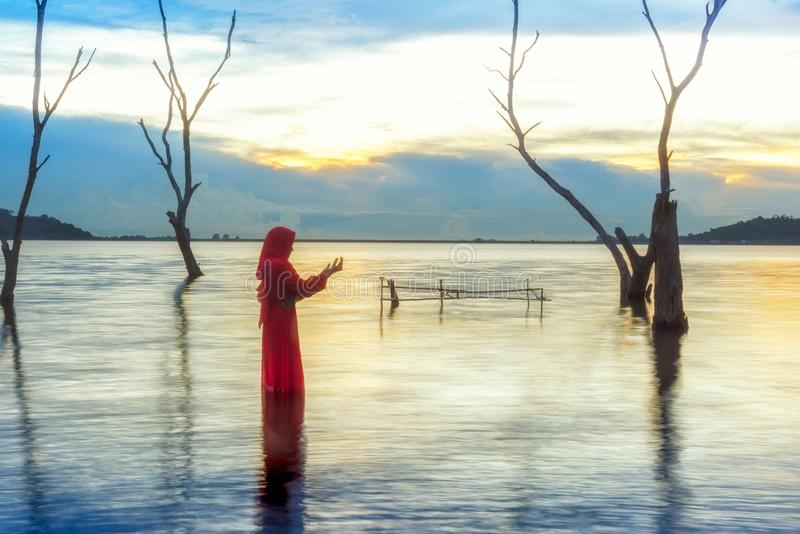 Veiled Islamic muslim woman wearing a burka standing and praying in the river royalty free stock photos